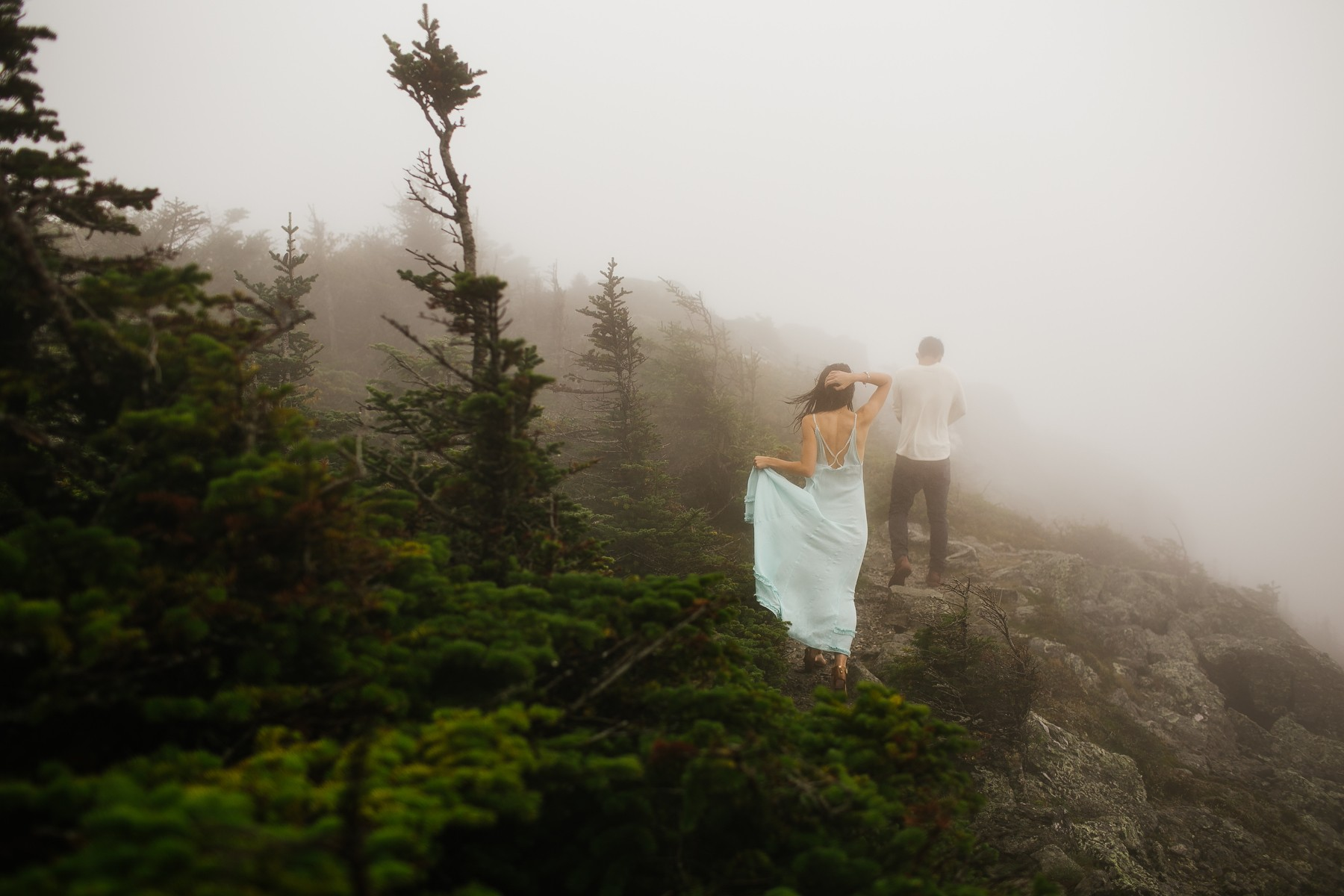 Couple walking on a path in the fog on Mt. Mansfield near Stowe, Vermont.